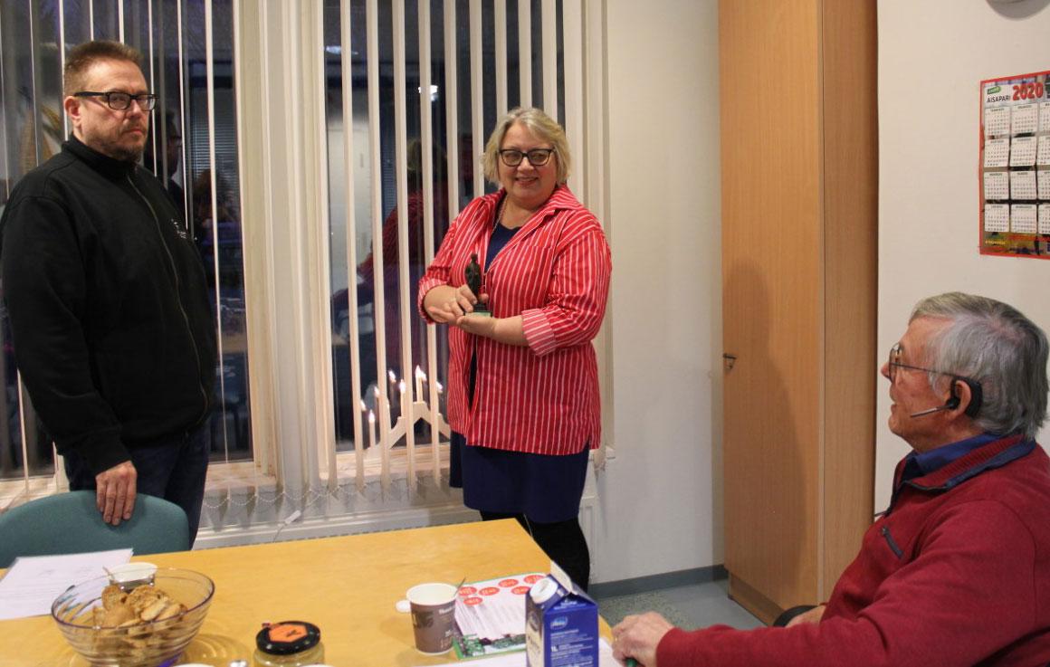 Kuvassa Hannu Takala luovuttaa Antti-patsasta Mervi Niemi-Huhdanpäälle ja pöydän ääressä istuu Mauri Jokela.