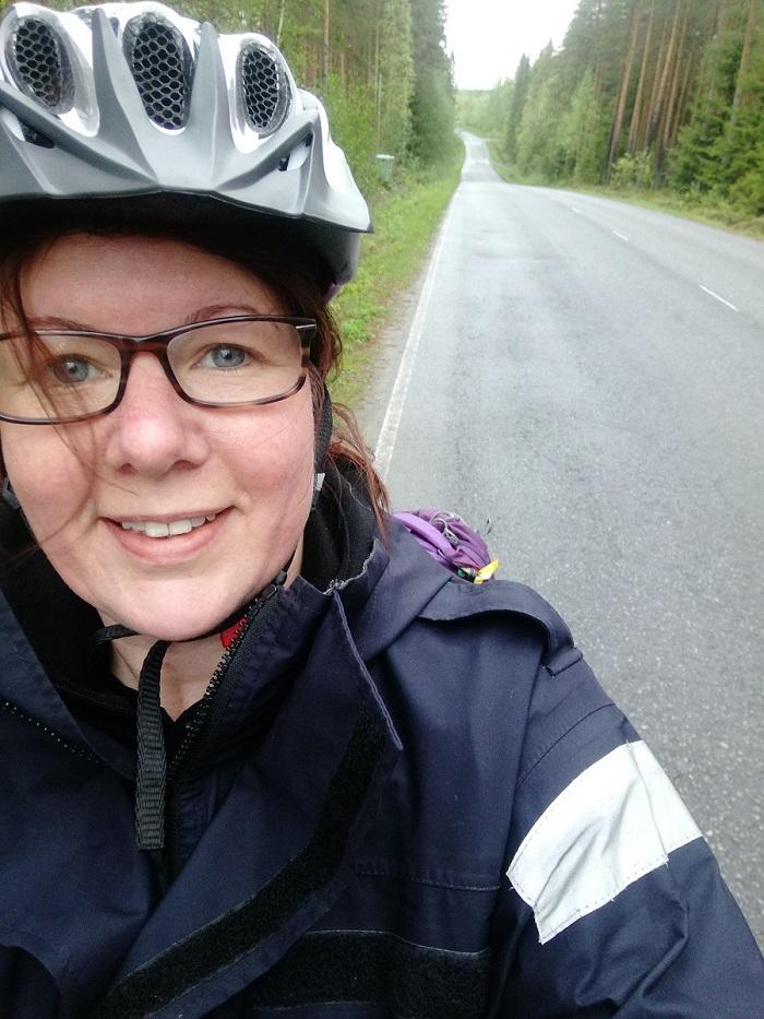 Hymyilevä nainen pyöräilykypärä päässään on ottanut itsestään kuvan maantien reunassa, mäen päällä.