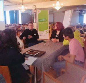 Viisi nuorta istuu pöydän ympärillä keskustelemassa annetusta aiheesta. Yksi tekee muistiinpanoja