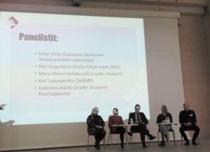 Viisi henkilöä istuu lavalla osallistuen paneelikeskusteluun. Seinälle on heijastettu panelistien nimet: Ismo Ulvila (Euroopan komission ilmastoasioiden pääosasto), Heli Seppelvirta (Etelä-Pohjanmaan Liitto), Mervi Niemi-Huhdanpää (Leader Aisapari), Kari Laasasenaho (Seinäjoen ammattikorkeakoulu) ja Katariina Arpala (Leader Aisaparin nuorisojaosto)