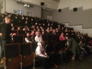 Ihmiset istuvat elokuvateatterin katsomossa odottamassa näytöksen alkua.
