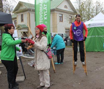 Kuva kylätapahtumasta, naisia juttelemassa ja yksi kävelee puujaloilla