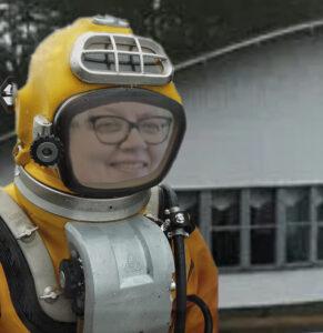 Kuvassa nainen keltaisessa sukelluspuvussa